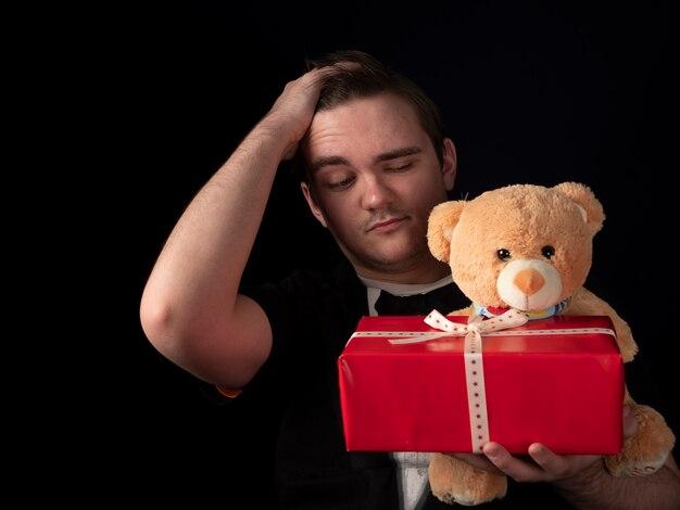 Молодой парень в черном костюме с футболкой держит красный подарок и плюшевого мишку, держащего голову рукой на черном.