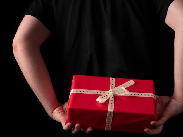Молодой парень в черном костюме с футболкой держит за спиной красный подарок на черном фоне