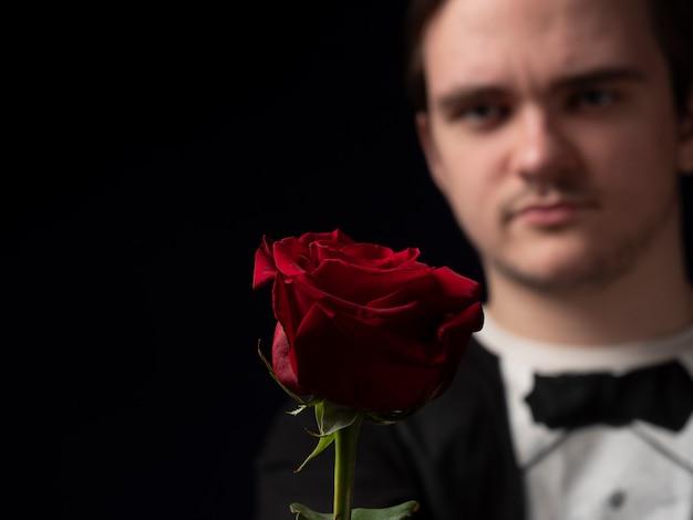 Молодой парень в черном костюме с футболкой держит в руках красную розу и показывает ее на черном
