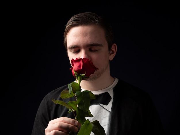 黒のtシャツのスーツを着た若い男が赤いバラを手に持って、黒に目を閉じてそれを嗅ぎます
