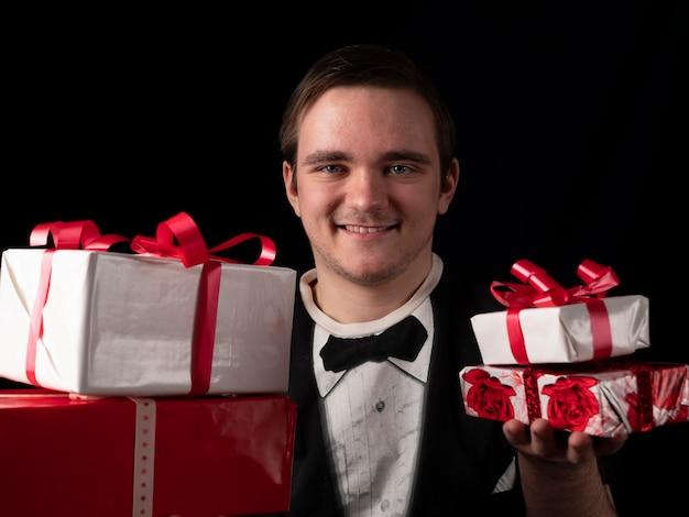黒のtシャツのスーツを着た若い男は、黒の手に赤と白の贈り物を持っています