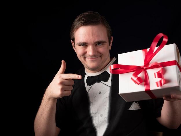 검은 티셔츠 정장을 입은 젊은 남자가 검은 색에 흰색 선물에 손가락을 보여줍니다.
