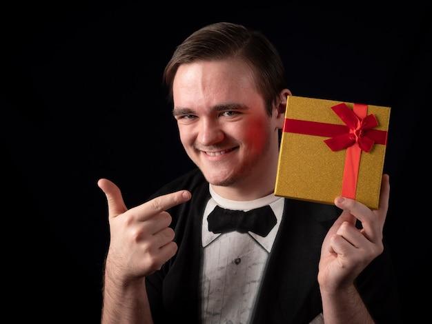 검은 티셔츠 정장을 입은 젊은 남자가 검은 색 노란색 선물에 손가락을 보여줍니다.
