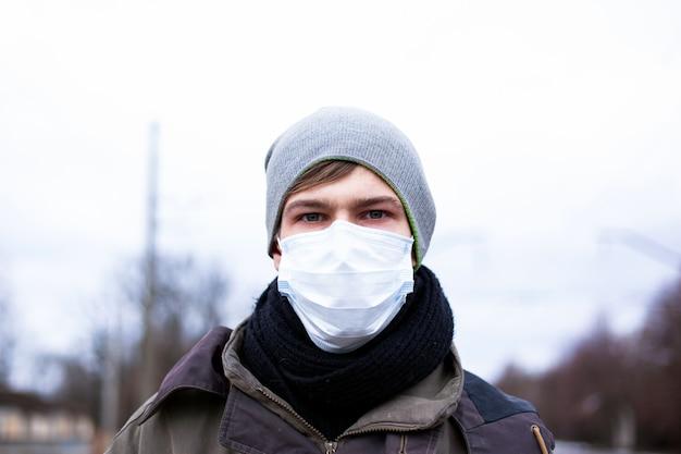 防護マスクを身に着けた若い男が、中国のウイルスのパンデミックであるコロナウイルスから身を守ります。 ncov-2019。