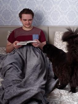Молодой парень в красной футболке сидит на светлой кровати и читает толстую книгу, концепция отдыха после рабочего дня