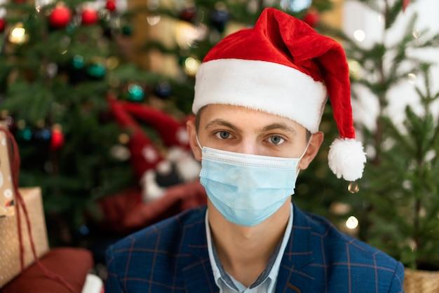 셔츠와 크리스마스 트리 배경에 산타 클로스 모자에 젊은 남자. 대유행 중 휴일
