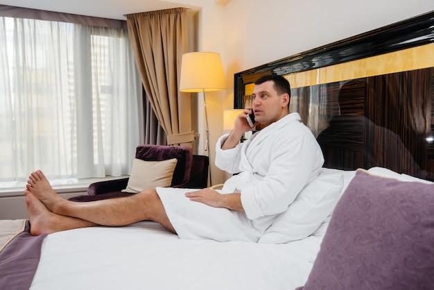 白い白衣を着た若い男がベッドに座ってホテルの部屋で電話で話している