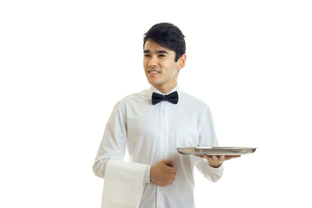 흰 셔츠와 검은 나비 넥타이를 입은 젊은 남자가 웃고 흰 벽에 고립 된 수건과 트레이를 들고 멀리 보인다.