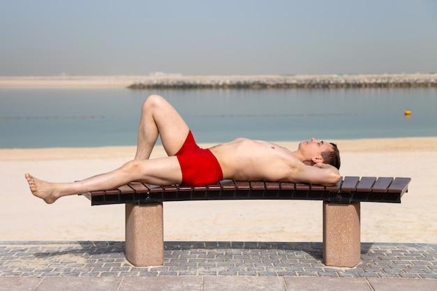 Молодой парень в красных плавках загорает, лежа на скамейке у пляжа.
