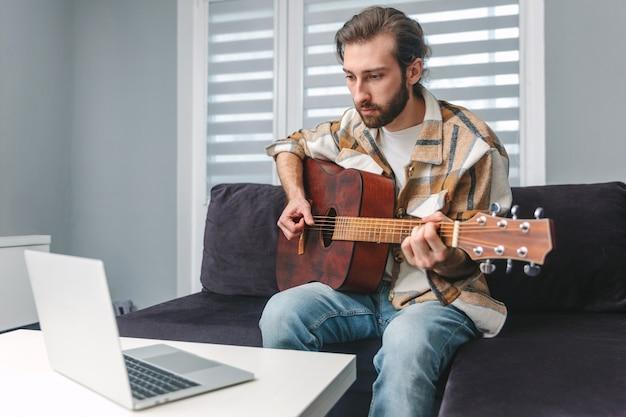若い男がギターを弾くことを学んでいます。オンラインレッスン。通信教育。