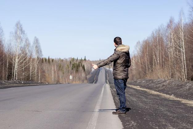한 젊은 남자가 재킷을 입고 길가를 걷고 있습니다. 이른 봄에 숲에서 ..
