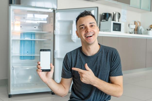 젊은 남자가 스마트 폰을 사용하여 음식을 주문합니다. 음식이없는 빈 냉장고. 음식 배달 서비스 광고.