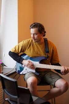 若い男が窓際に座ってエレキギターを弾く