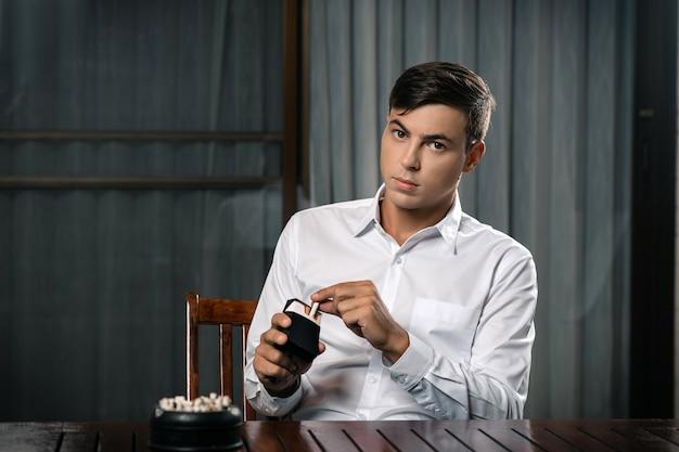 Молодой парень позирует сидя за столом, на котором стоит пепельница