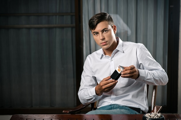 Молодой парень позирует сидя за столом, на котором стоит пепельница, полная сигарет
