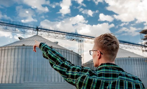Молодой парень стоит возле зернохранилища и показывает рукой