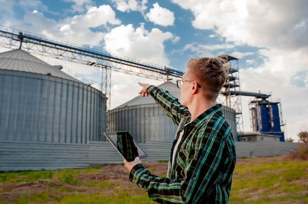 若い男が農業地帯の金属製エレベーターの近くにタブレットを持って立っています。穀物倉庫。
