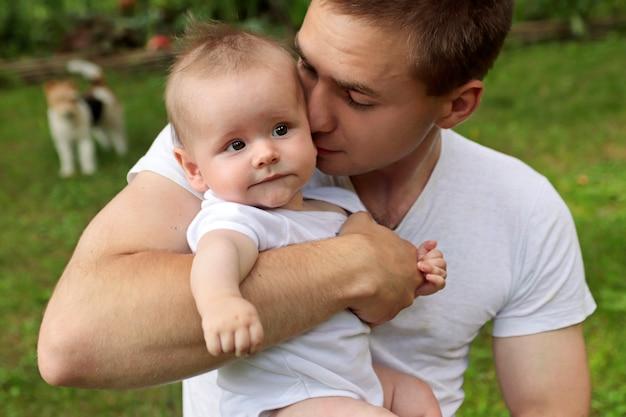 Молодой парень прикасается к щеке своего родственника маленького ребенка.