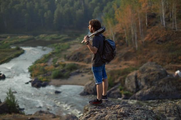 젊은 남자 여행자가 언덕 꼭대기에 서서 우쿨렐레를 들고 높은 품질의 거리를 바라보고 있습니다.