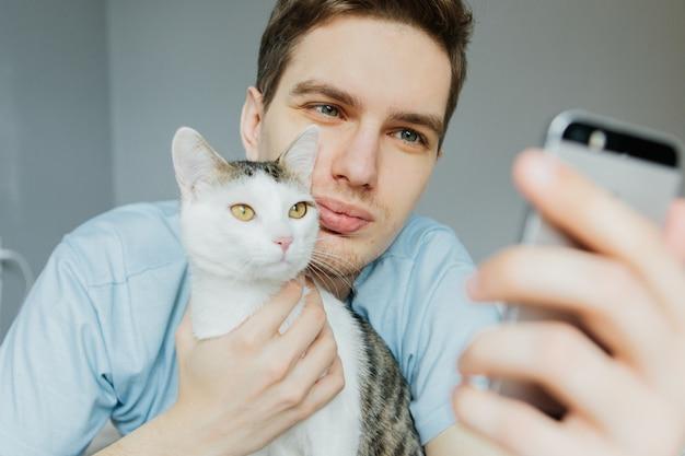 Молодой парень с кошкой разговаривает по видеопередаче, общение. карантин