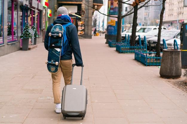 스케이트와 플라스틱 트롤리 가방을 든 젊은 남자가 도시의 거리를 갑니다. 스케이팅 선수. 도시의. 여행자. 십대. 여행. 여행. 걷다. 보도. 스케이트보드. 스케이트보더. 유행을 좇는 사람. 뒷모습