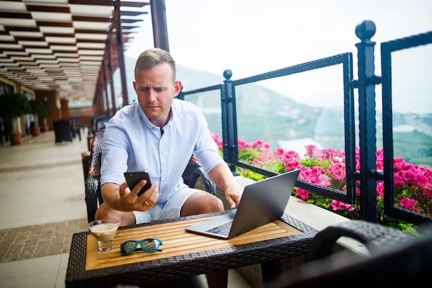Молодой красивый бизнесмен в белой рубашке и шортах сидит с ноутбуком в кафе за столом и разговаривает по телефону. работайте во время отдыха