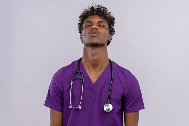 Молодой красивый темнокожий доктор с вьющимися волосами в фиолетовой форме со стетоскопом закрывает глаза с усталым выражением лица