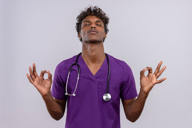 Okのサインを見せながらリラックスした聴診器で紫の制服を着た巻き毛の若いハンサムな浅黒い医者
