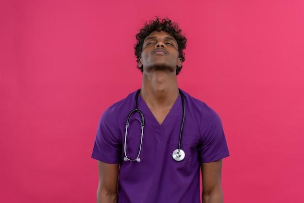 聴診器で疲れた感じの紫の制服を着た巻き毛の若いハンサムな浅黒い医者