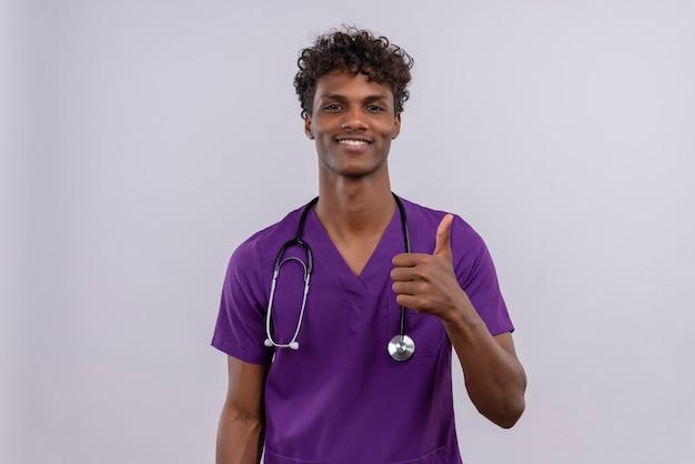 親指を現しながら幸せな聴診器で紫の制服を着た巻き毛の若いハンサムな浅黒い医者