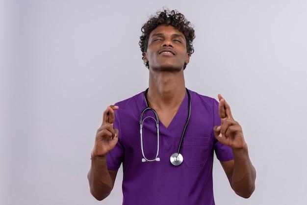 リラックスした感じの指を一緒に保持している聴診器で紫の制服を着ている巻き毛の若いハンサムな浅黒い医者
