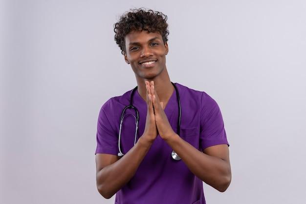 感謝のジェスチャーで一緒に手を繋いでいる聴診器で紫の制服を着た巻き毛の若いハンサムな浅黒い医者