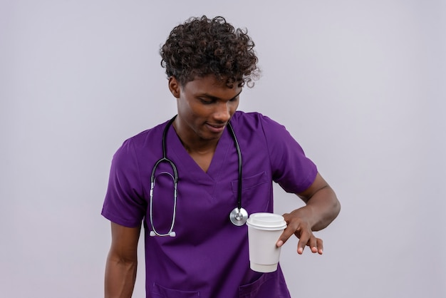 コーヒーの紙コップを見て聴診器で紫の制服を着ている巻き毛の若いハンサムな浅黒い医者
