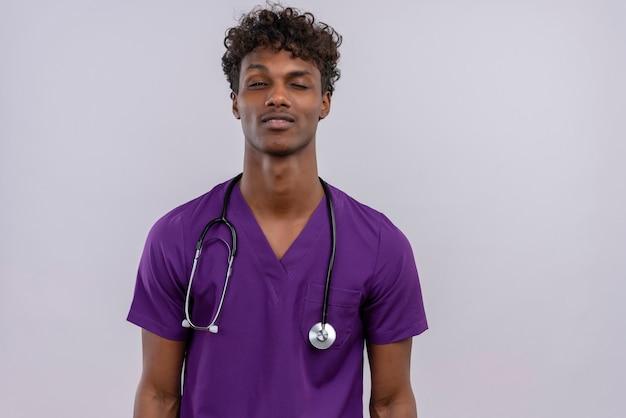 Молодой красивый темнокожий врач с вьющимися волосами в фиолетовой форме со стетоскопом подмигивает одним глазом