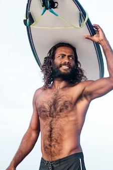 서핑보드를 들고 있는 젊고 잘생긴 검은 피부의 남자