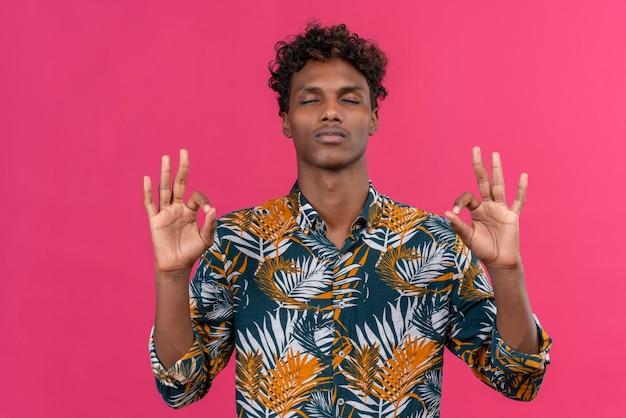 Молодой красивый темнокожий мужчина с кудрявыми волосами в рубашке с принтом листьев держится за руки в знаках ок и держит глаза закрытыми в расслаблении и медитации