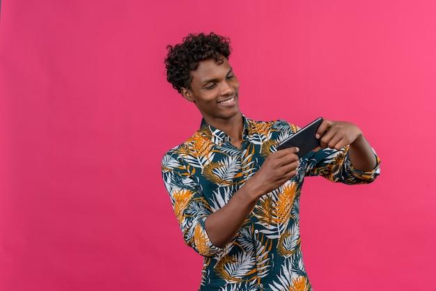 携帯電話でゲームをしている葉のプリントシャツに巻き毛の若いハンサムな浅黒い肌の男