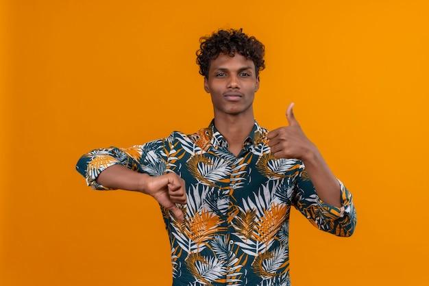Молодой красивый темнокожий мужчина с вьющимися волосами в рубашке с принтом листьев показывает большие пальцы руки вверх и вниз
