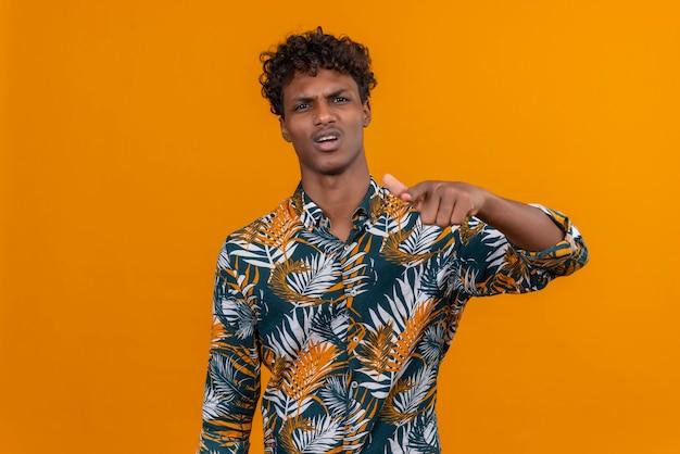 Молодой красивый темнокожий мужчина с кудрявыми волосами в рубашке с рисунком из листьев с сердитым и агрессивным выражением лица указывает в камеру указательным пальцем