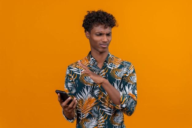 携帯電話を持って怒りの表情で葉プリントシャツに巻き毛の若いハンサムな浅黒い肌の男