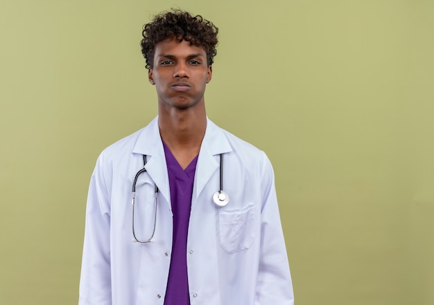 緑の空間で疲れを感じている聴診器で白いコートを着た巻き毛の若いハンサムな浅黒い肌の男
