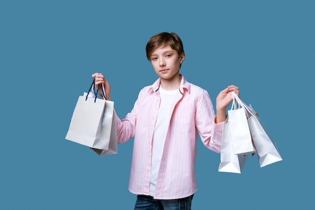 Молодой красивый парень держит в руках бумажные пакеты с покупками на синей стене