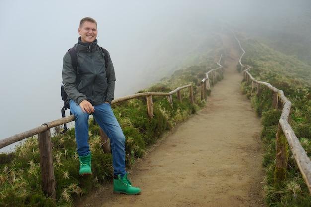 Молодой красивый парень стоит на краю обрыва на тропинке, всюду покрытой туманом.