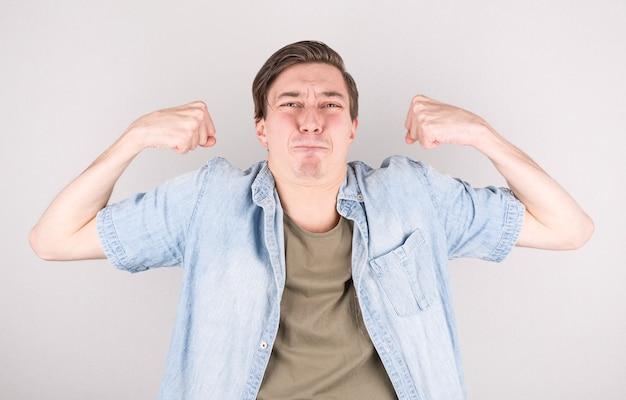若いハンサムな男は、柔軟な形と筋肉の上腕二頭筋で、非常に懸命に、幸せで、強くしようとします、白い壁に対してジムの後に強く見えます