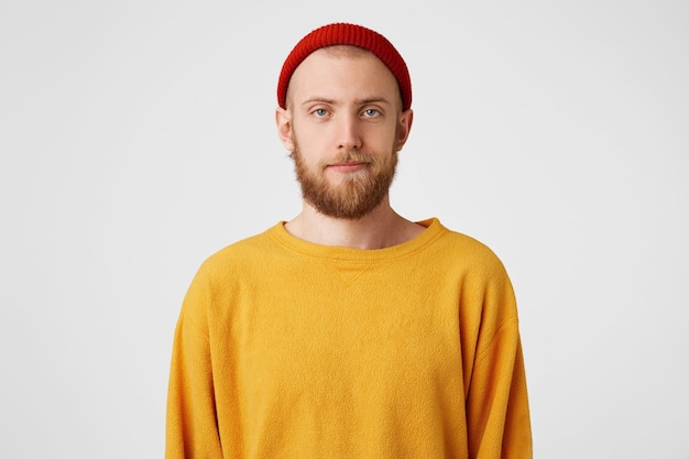 あごひげと青い目をした若いハンサムな男は、無関心で、不満を持って、無関心な顔で立っています