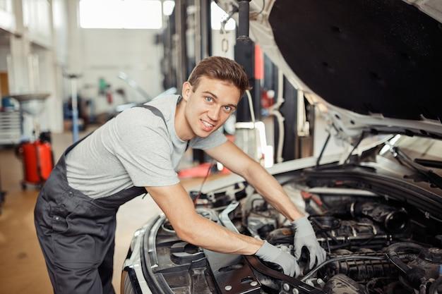 Молодой красавец проверяет двигатель автомобиля в автосервисе.