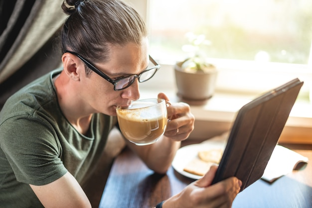 가제트 태블릿을 사용하여 인터넷에서 흥미로운 뉴스를 읽는 젊은 잘 생긴 남자