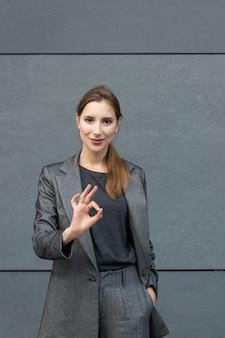 事務所ビルの背景に灰色のビジネススーツで若いハンサムな女性が立っています。自信を持って成功するビジネスウーマンのコンセプト。
