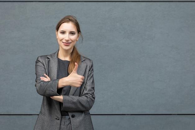 Молодая красивая женщина стоит в сером деловом костюме на стене офисного здания. концепция успешной, уверенной в себе деловой женщины.