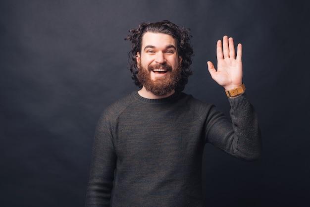 Молодой счастливый бородатый мужчина улыбается и машет рукой